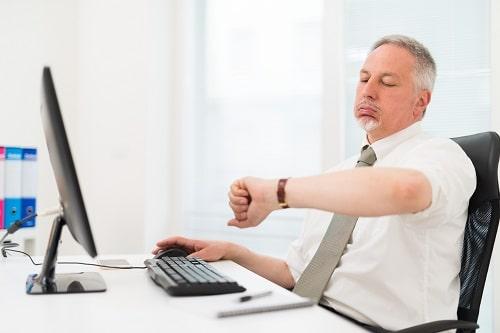 Homme qui soupire en regardant sa montre