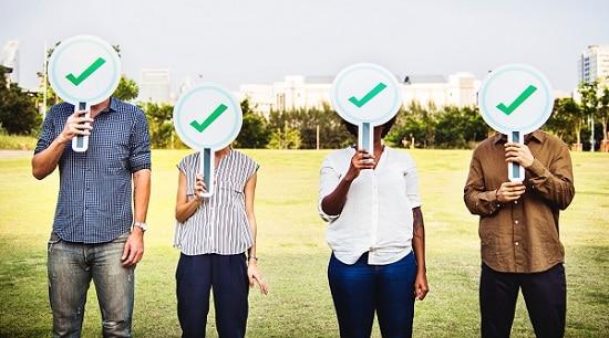 Adultes tenant des panneau avec des coches vertes