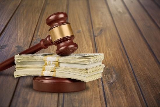 Liasses de billet sous un marteau d'avocat