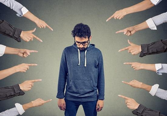 Homme qui se fait pointer du doigt