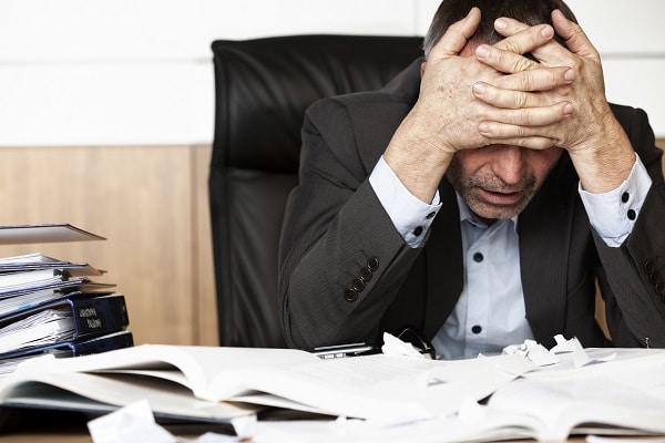 Homme qui semble dépité devant un bureau remplit de papiers et documents